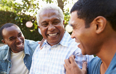 Image of senior man talking with his adult sons in garden, close up