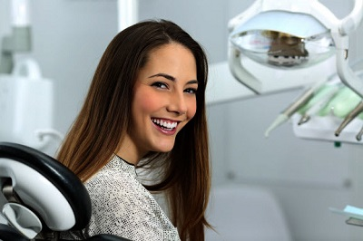 Woman smiling while sitting in dental chair