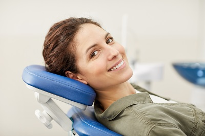 Portrait of smiling young woman lying in dental chair and looking at camera