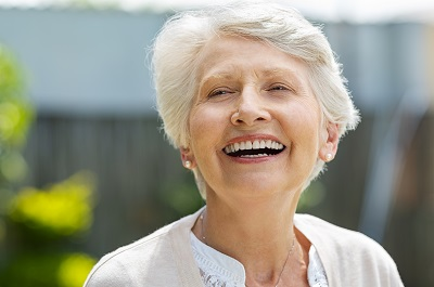 Portrait of a beautiful senior woman laughing outdoor.