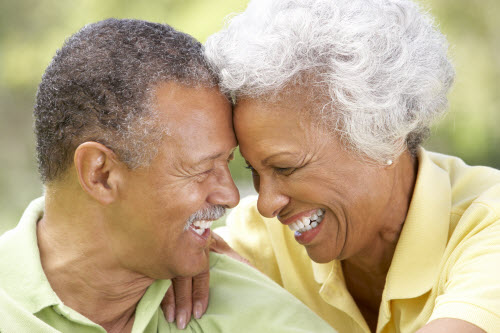 Elderly man and woman laughing together touching heads
