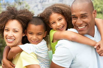 african american family smiling at the camera in the park