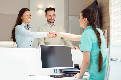 patient shaking hands with receptionist