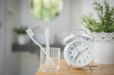 Toothbrush in glass next to a clock
