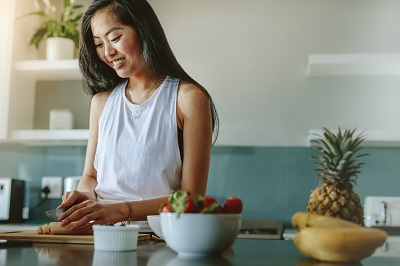 asian woman preparing healthy meal with fruits