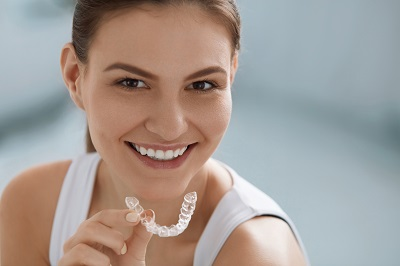 smiling woman holding clearcorrect aligners