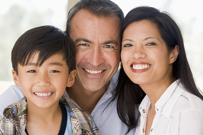 mixed race family of three smiling
