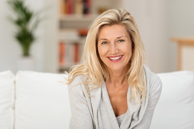Lovely middle-aged blonde woman with a beaming smile sitting on a sofa