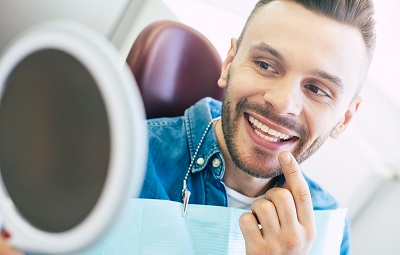 Image of male patient checking out his smile after teeth whitening treatment