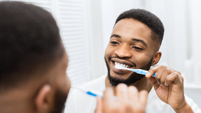 Image of African American man brushing teeth at home