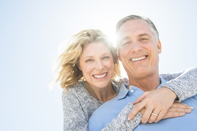 Low angle portrait of cheerful mature woman embracing man from behind against clear sky