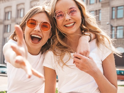 two young beautiful blond smiling girls in trendy summer white t-shirt clothes