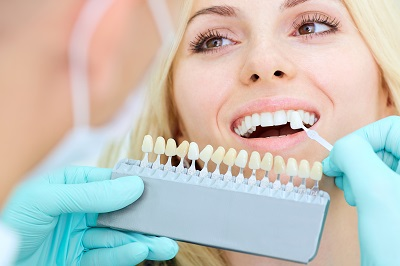 closeup of dentist helping patient pick veneers