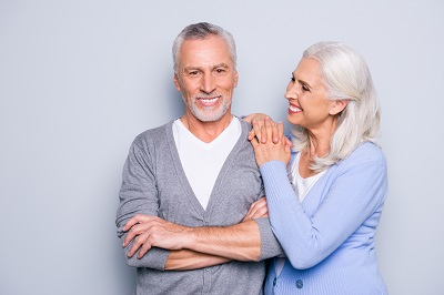 smiling senior couple with grey background