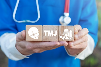 dentist holding sign that says TMJ