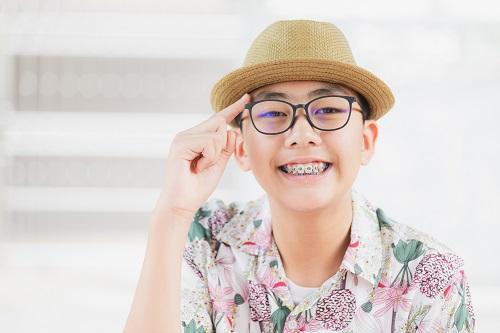 young boy with glasses smiling over white background
