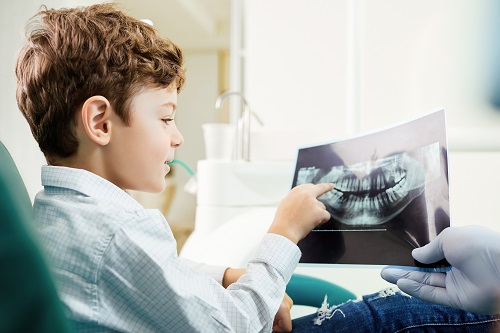 A child in the dental office looking at dental x-ray