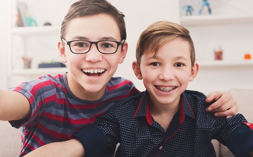 Two handsome teenage boys taking selfie while posing with smile to phone at home. Wearing glasses and braces.