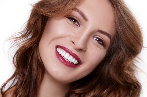 Beautiful face of young smiling brunette woman with clean fresh skin and perfect teeth
