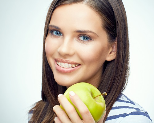 Close up smiling face portrait of young woman with braces on teeth holding green apple