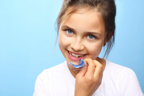 little girl holding retainers