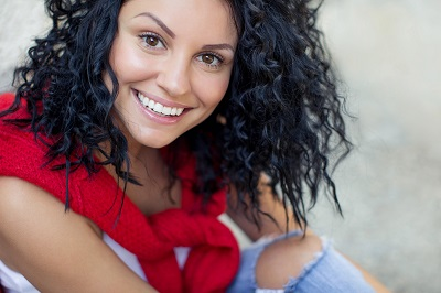 smiling young woman with dark curly hair