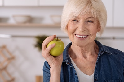 Close up of a cheerful elderly woman holding an apple while standing in the kitchen