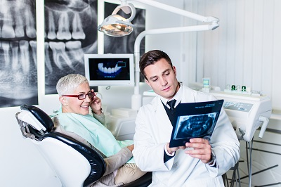 Image of senior man with glasses consulting at dental clinic if he needs implants
