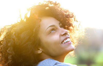 Close up portrait of a beautiful young african american woman smiling and looking up
