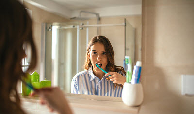 Portrait of a beautiful woman brushing teeth and looking in the mirror in the bathroom.