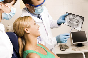 Picture of a woman and her dentist going over an x-ray for root canal therapy in Yonkers and Bronxville