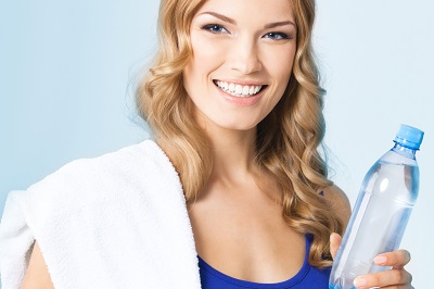 Portrait of cheerful young attractive blond woman in fitness wear with bottle of water and towel, over blue background