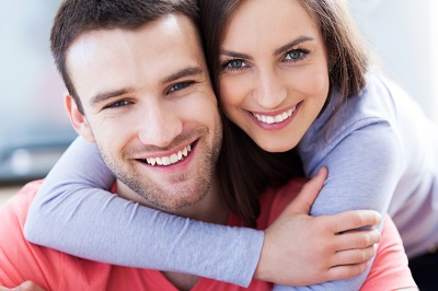 Young couple with healthy smiles hugging