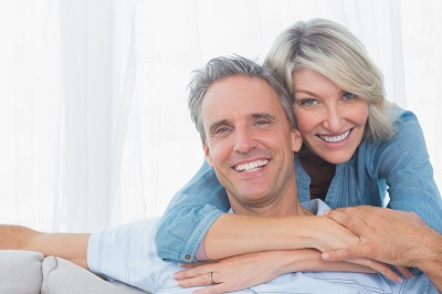 mature couple smiling at the camera at home in living room