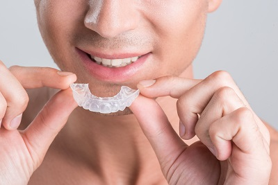 man holding invisalign clear braces