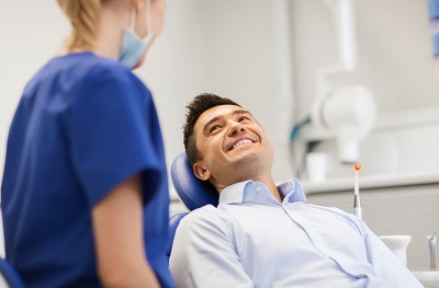 male patient at dental chair discussing treatment options