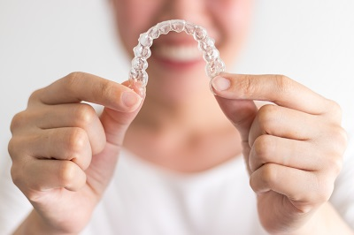 close up of woman holding invisalign braces