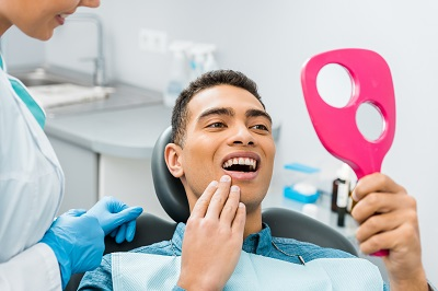 cheerful african american man looking at mirror checking out his smile in dental office