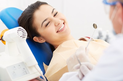 smiling patient at dental office getting a dental inspection