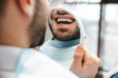 patient checking out his smile after getting in-office teeth whitening