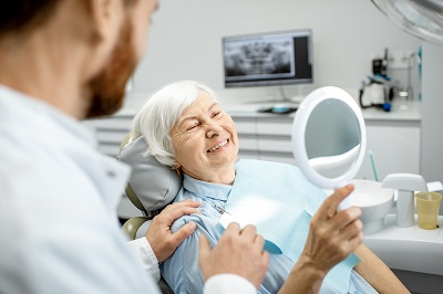 senior woman checking out her new smile with dental implants at dental office
