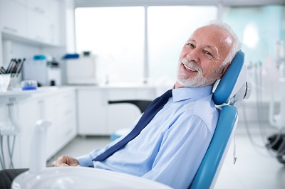 happy senior man sitting at dental chair