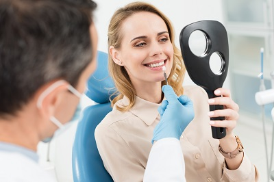 female patient checking her smile with hand mirror at dental office