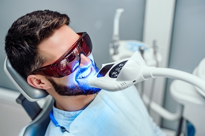 young man getting teeth whitening procedure at dental office