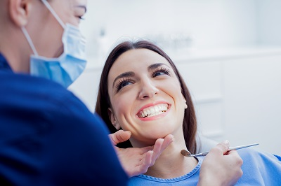 woman patient getting her teeth examined