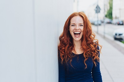 young redhead woman laughing while leaning against while wall in the streets