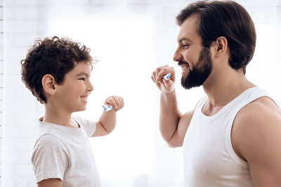 Happy father and son brush teeth, looking at each other.
