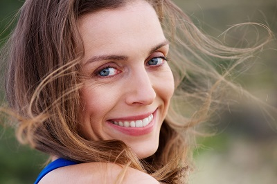 Close up portrait of healthy smiling woman outside