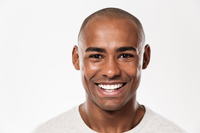Image of handsome smiling young african man standing isolated over white background.