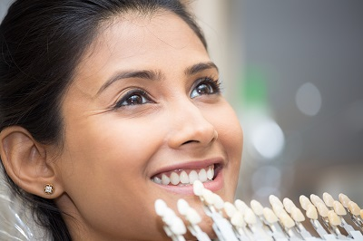 Closeup portrait of young woman getting shade of teeth selected by dental professional for veneer treatment purposes